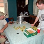 Two male gamers play a tile-based board game.