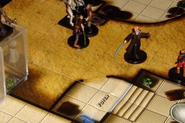 Star Wars-themed miniatures face off on a desert-colored battle map. A Saga Edition rulebook appears to the lefthand side.