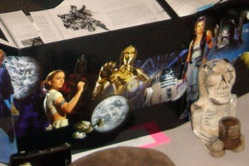 Various scenes from the Star Wars movies cover a game master screen. In front of the screen is a small ceramic statue; behind it are several Star Wars books.