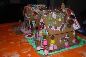 Two gingerbread houses, each covered in candy, stand side by side on an orange tablecloth.