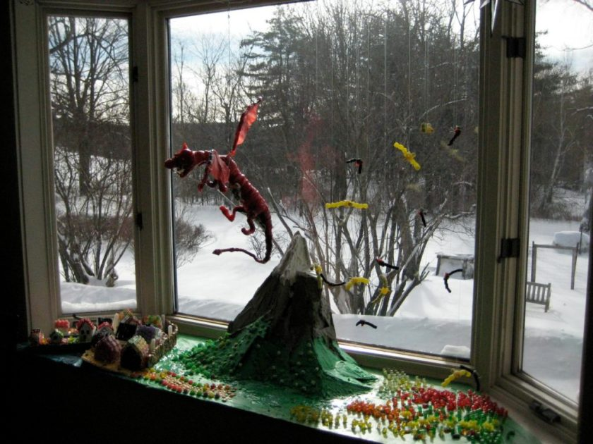 A candy red dragon flies over a large mountain. Below, gummy bear warriors prepare to fight.