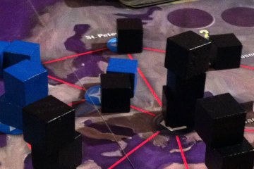 Black and blue cubes -- representing viruses -- are stacked on a map-like game board depicting various cities. A white pawn represents the player character fighting the viruses.