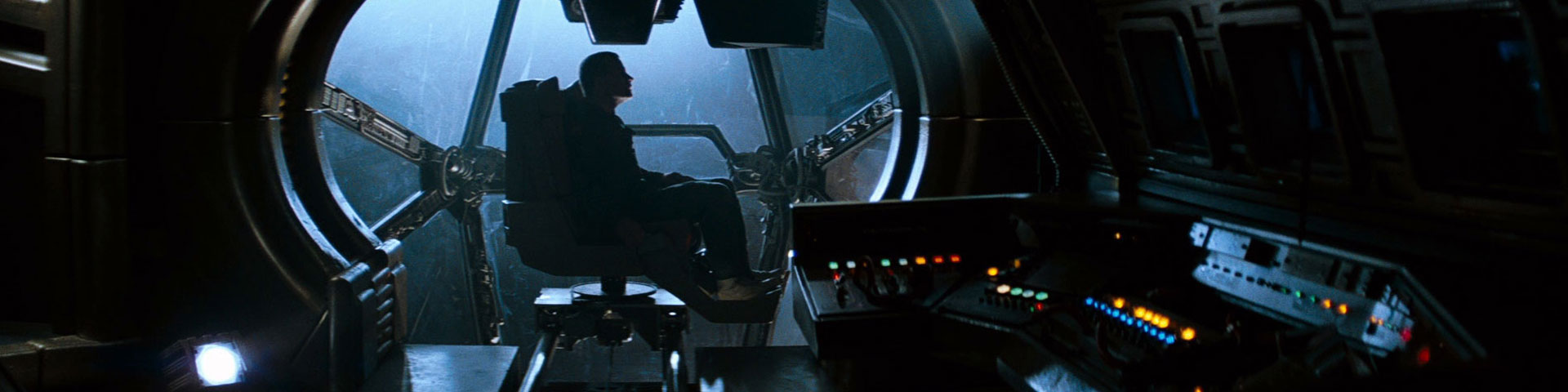A lone individual sits in an observation bubble on a starship, surrounded by dingy, beat-up computer equipment.