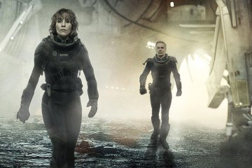 Three space-suited individuals walk out of a starship that has landed on an alien planet.