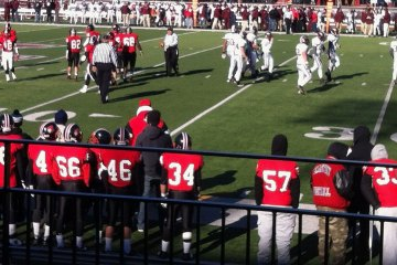 Red-jerseyed high school football players line the sidelines.