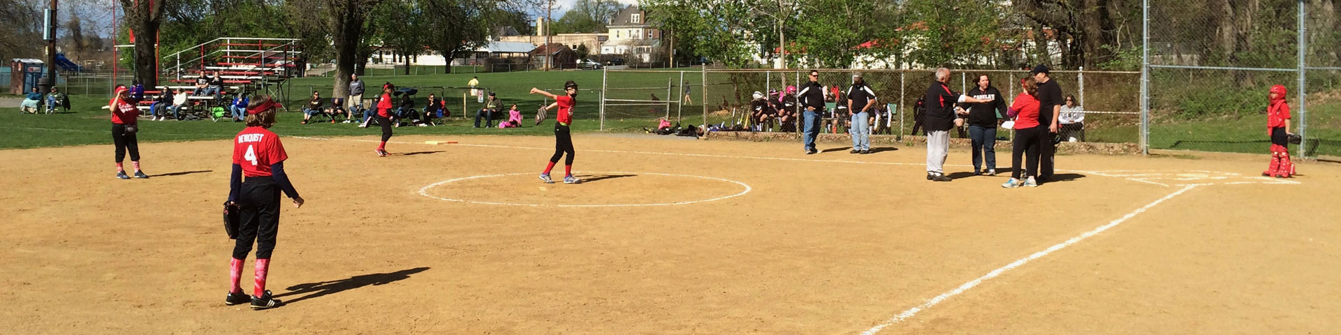 Girls get ready to field the ball during a softball game.