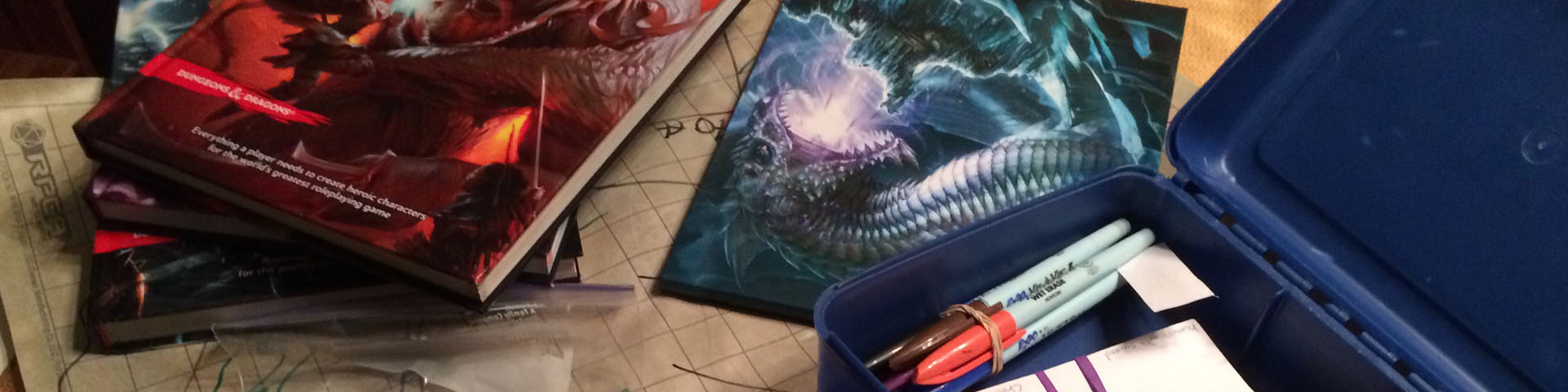 A stack of D&D 5th Edition books, a 5e DM screen, and my gaming lunchbox.