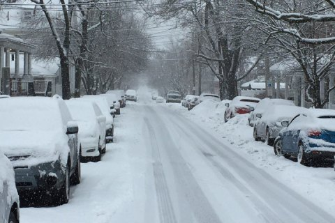 A snow-covered city street lined with cars.