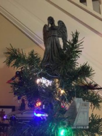 A close-up of the geek tree topper: the Weeping Angel from Dr. Who. The angel is about 8 inches tall, with a grey body, wings, and hands covering her face.