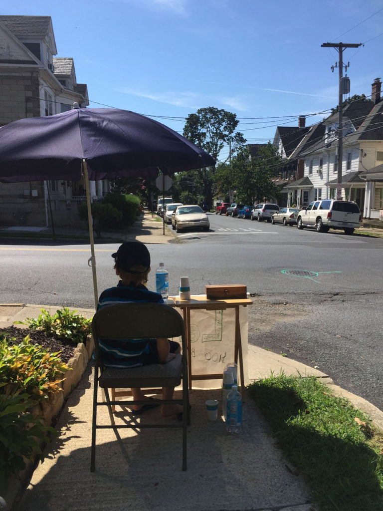 A young boy sits under an umbrella while he sells lemonade at a stand. A city street is in the background.