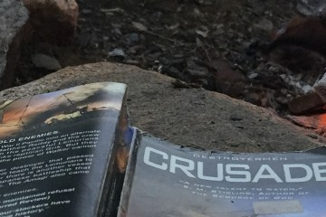 "The paperback book ""Crusade"" lies face down on a rock next to a fire."