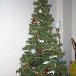 A small Christmas tree with a number of geeky ornaments. The tree is not lit.