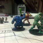Large, frog-like figurines representing different colored slaadi monsters threaten player character miniatures.
