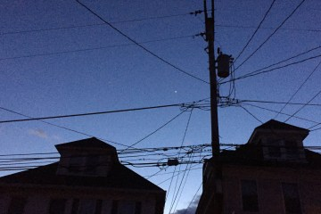 A bright planet - Venus -- appears against a darkening blue sky. Shadowed buildings and phone lines appear in the foreground.