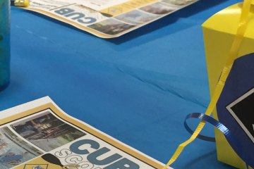 An activity worksheet and a yellow box stand against a blue table cloth