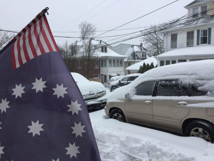 An blue flag with white stars is in the foreground, while snow covered cars appear in the background.