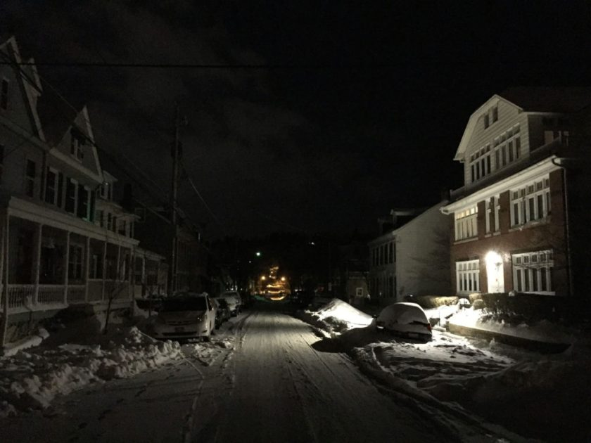 Streetlights illuminate a snowy street.
