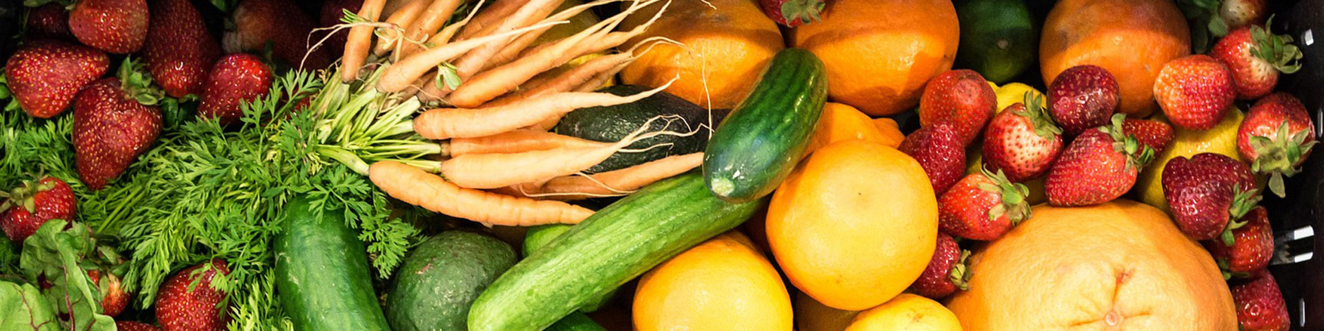 An assortment of vegetables and fruit including carrots, squash, oranges, and strawberries.
