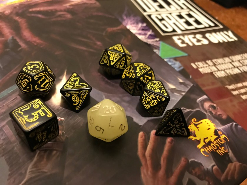 Black dice with yellow lettering appear on role-playing book covers. A single yellow-ish glow-in-dark d20 amid them.