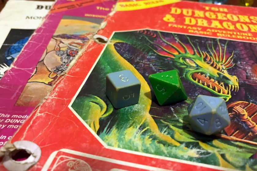 Three old dice - two blue, one green - are laying on top of several battered role-playing game supplements from the 1980s.