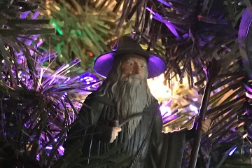 Three ornaments - Darth Vadar, the wizard Gandalf, and the starship Enterprise - appear on a Christmas tree.