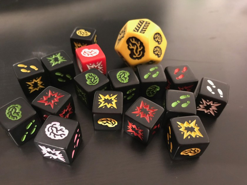 Zombie-themed dice on a black tabletop. The dice have three types of faces: brains, shotgun, and feet. There's also large yellow d12 representing a school bus.