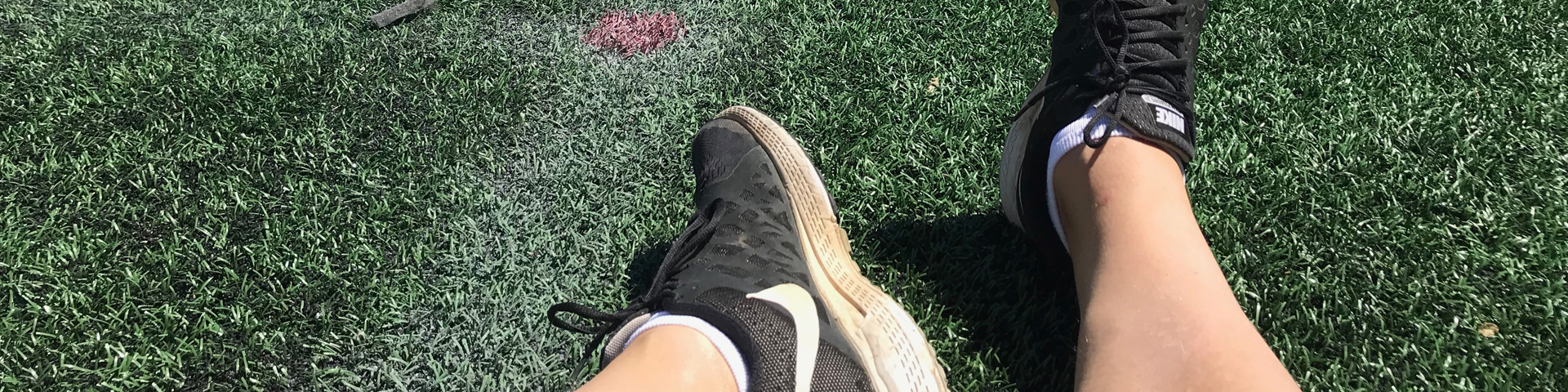 My be-sneakered feet resting on a field.