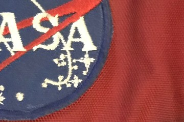 A close-up view of my old red backpack with a NASA patch on it.