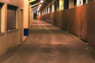 The passageway underneath the stadium seating. A chainlink fence is on the right; closed and shuttered food service areas are on the left.