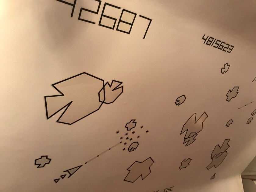 The ray-drawn shapes of asteroids appear on a white wall.