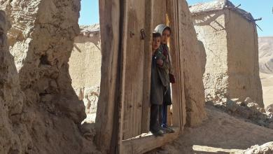 Children stand at the entrance gate to their house after an earthquake, in Farkhar district of Takhar province, Afghanistan