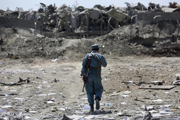 """An Afghan Security policeman inspects the site of a suicide truck bombing, in Kabul, Afghanistan, Monday, Aug. 1, 2016. Afghan authorities say an overnight attack on a guesthouse for foreign contractors claimed by the Taliban has killed at least one policeman and wounded several others. The Interior Ministry says """"terrorists"""" used a truck full of explosives to breach the wall of the hotel around 1:30 a.m., then three gunmen entered the premises and started shooting. (AP Photos/Rahmat Gul)"""