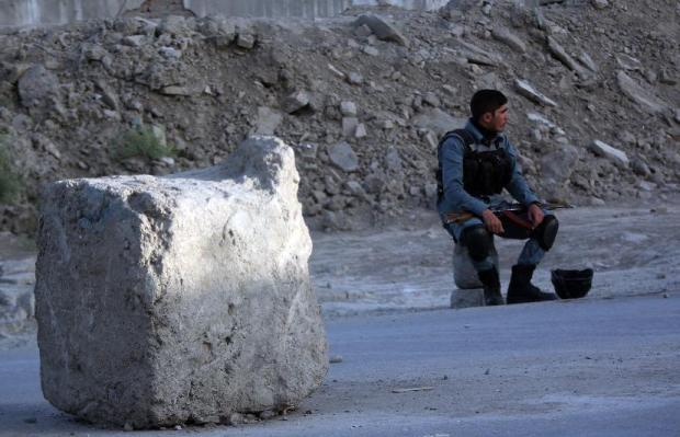 An Afghan police guards around a road leading to the site of an explosion, in Kabul, Afghanistan, Monday, Aug. 1, 2016. A strong explosion took place early Monday near a guesthouse for foreigners in Kabul, an Afghan police official said. (AP Photos/Massoud Hossaini)