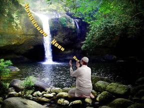 man chanting near waterfall