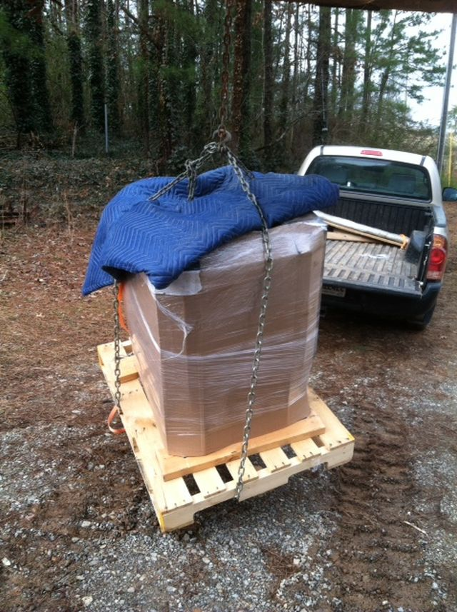 the pallet and a moving blanket protect the stove from damage from the lifting chains