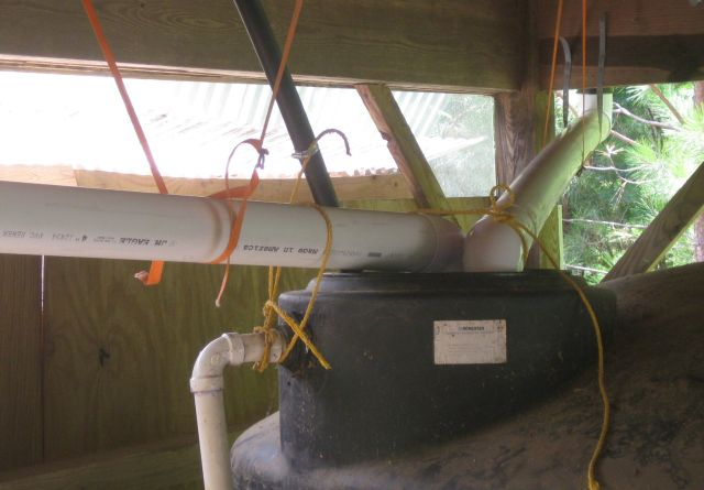 """the two 4"""" pipes feed directly into the top of the tank and are secured with straps and rope"""
