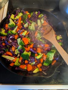 carrots, broccoli, and cabbage in a cast iron pan