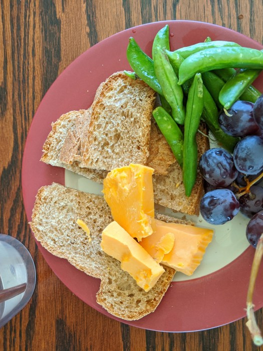 plate with bread, cheese, grapes, and snap peas