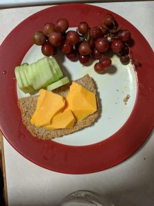 cucumber slices, bread, cheese, and grapes on a plate