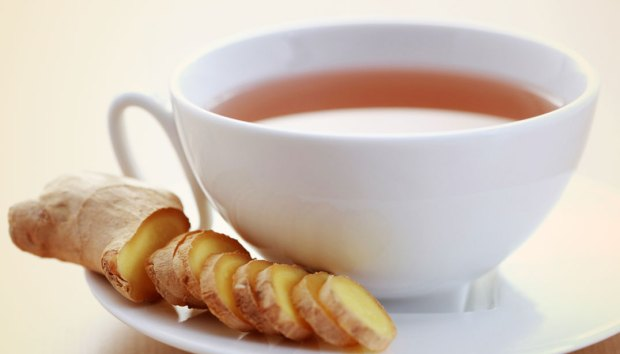 Cup of ginger tea with sliced ginger.