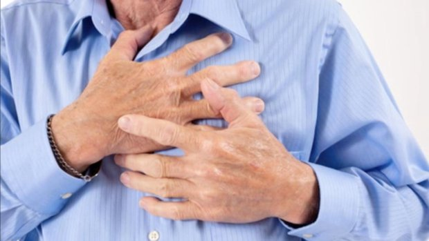 Man clutching his chest as he has a heart attack.