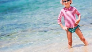 ビーチでラッシュガードを着ている子供の女の子