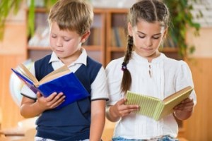 小学生低学年の男女が本を読む