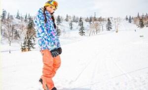 ゲレンデでスノボウェア上下セットを着用する女性