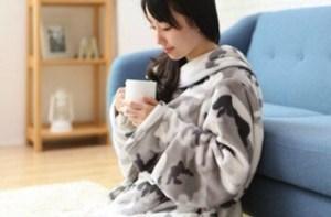 着る毛布を着て、コーヒーを飲む女性