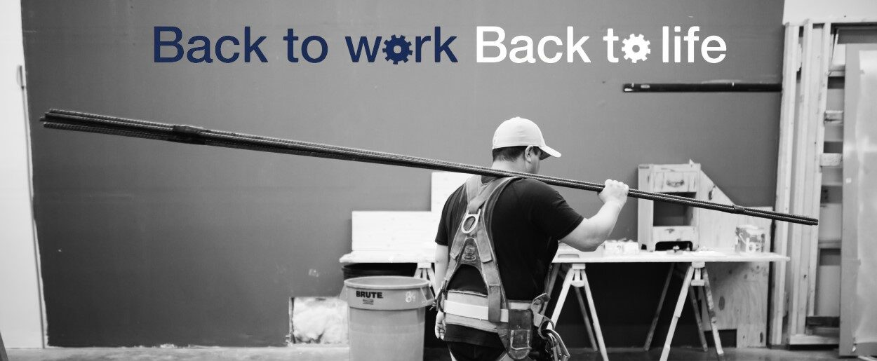 """Black and white photo of man carrying long piece of iron rebar with company slogan """"Back to work, back to life"""" above him."""
