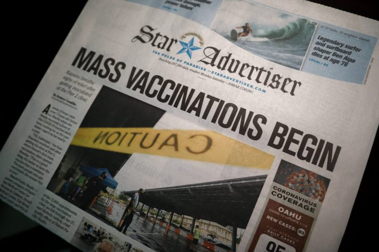 """A newspaper article with the headline """"mass vaccinations begin"""""""
