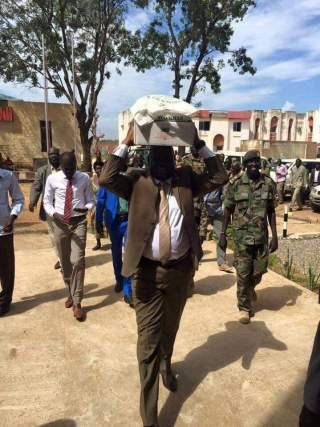 South Sudan's TNLA Speaker, Hon. Anthony Lino Makana carrying his ration from food donated by China(Photo credit: supplied)
