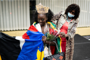 Pageant organizer Yar Kang drapes the South Sudanese flag over the shoulders of Nyakuaar Koang after she was named Miss South Sudan USA 2021 in Bloomington, Minn., on Saturday, Oct. 24, 2020.Evan Frost | MPR News