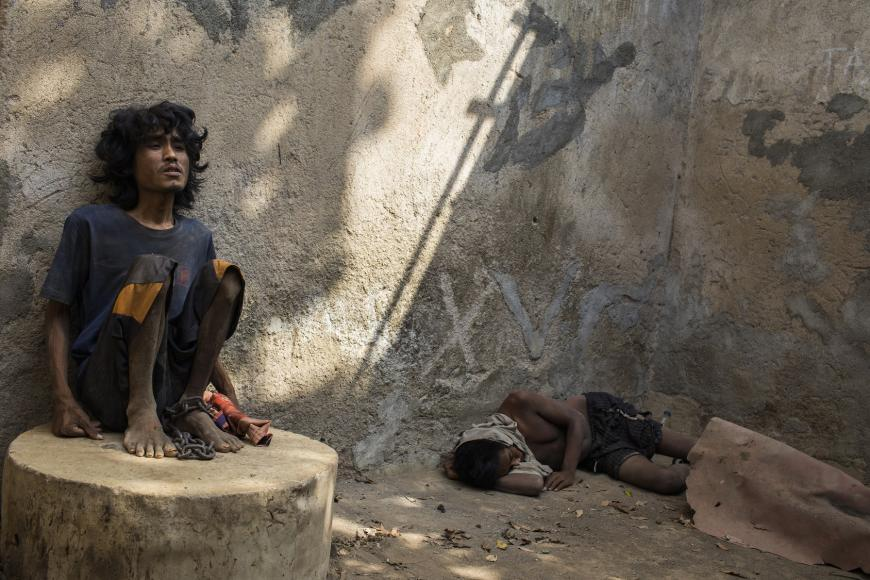 """Muji, a 24-year-old man with a mental health condition, has been living in chains for months at Marsiyo's House, a private family-run institution in Kebumen, Central Java, Indonesia. When this photo was taken, Muji said he was """"very, very hungry"""" and, pointing to the chain around his ankle, said it is """"against human rights."""" © 2019 Andrea Star Reese"""